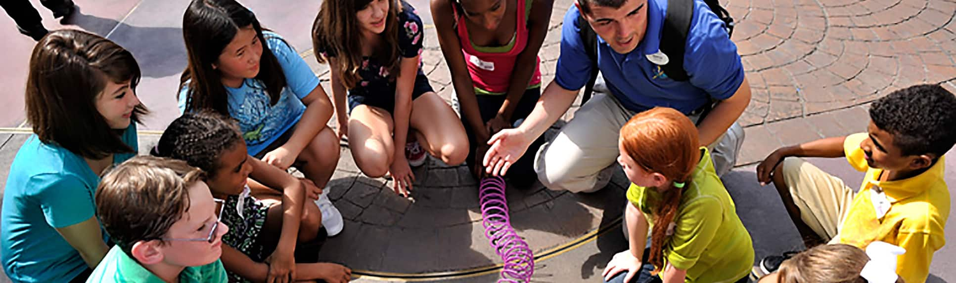 Children holding a Slinky in a circle with a Cast Member