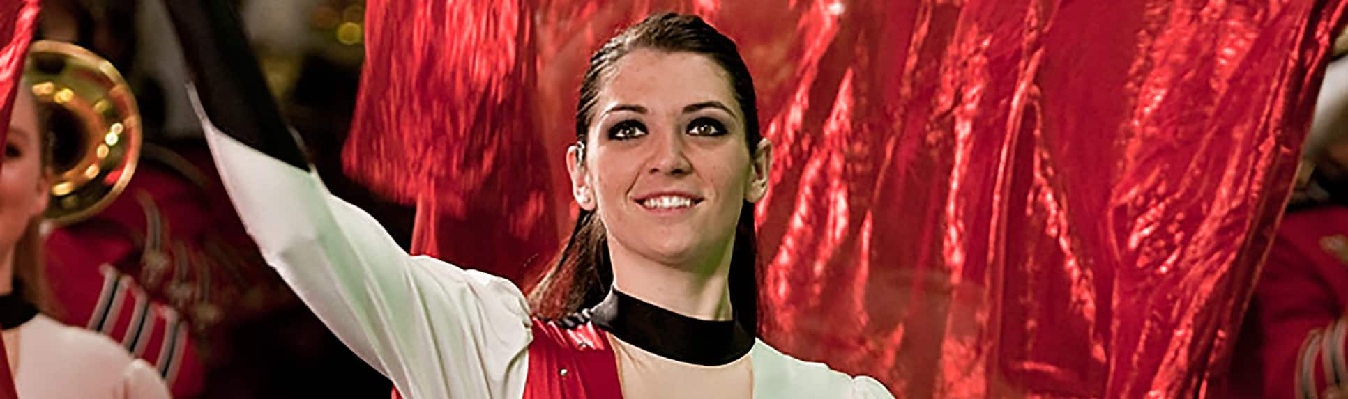 A smiling performer wearing a uniform
