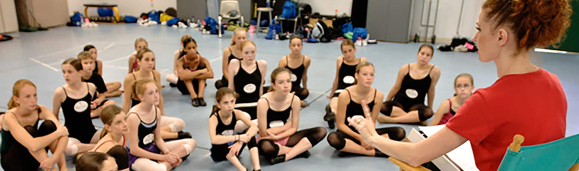 A woman sitting in a directors chair looking at a group of young girls wearing dance clothes and jazz shoes