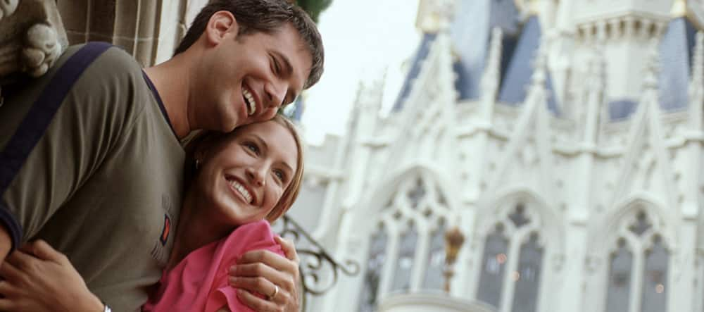 A man and woman embrace by Cinderella Castle at Magic Kingdom park in Florida