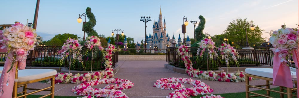 Cinderellas Castle Stands In The Background Of An Outdoor Wedding Venue Set With Chairs And Floral