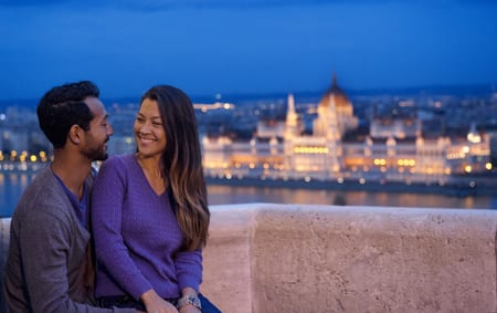 A man and a woman cuddle on a balcony at dusk with the city in the background
