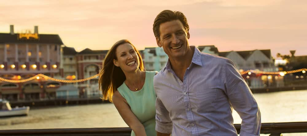 A man and woman share a laugh together on the boardwalk at sunset