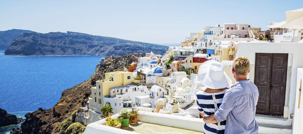 A man and a woman gazing at the hillside homes on the island of Santorini