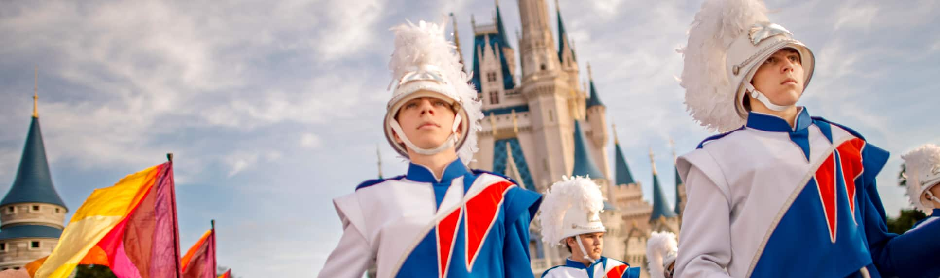 Flag wavers and drummers march in a parade near Cinderella Castle