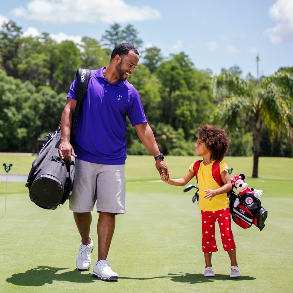 A father and young daughter holding hands while walking on a golf course with their golf bags