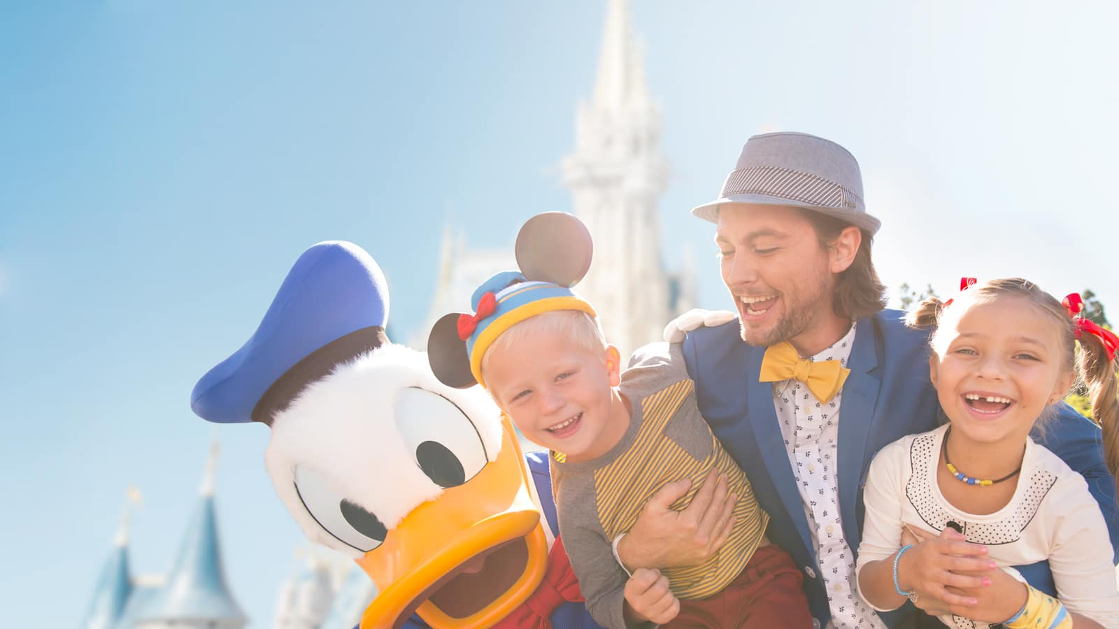 A father, daughter and son standing beside Donald Duck near Cinderella Castle