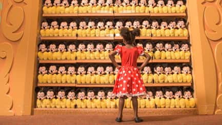 A little girl in a store gazing at a shelf of Mickey Mouse plush toys