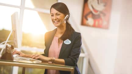 A Disney Cast Member wearing a telephone headset and typing at a computer