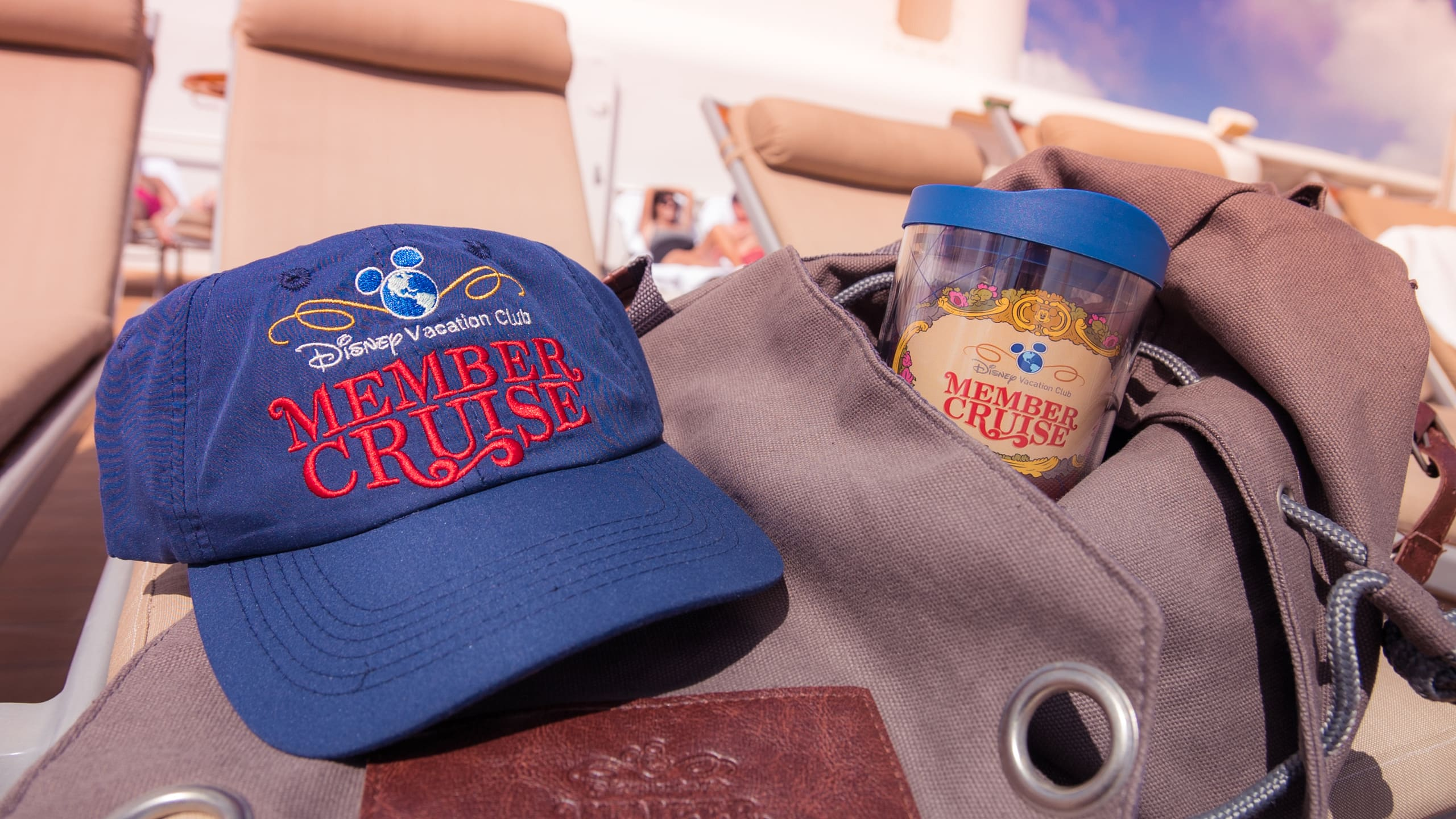 A baseball cap and a tumbler with the Disney Vacation Club Member Cruise logo