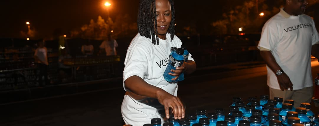 Along the race route, 2 volunteers fill a table with water bottles to hand out to passing runners